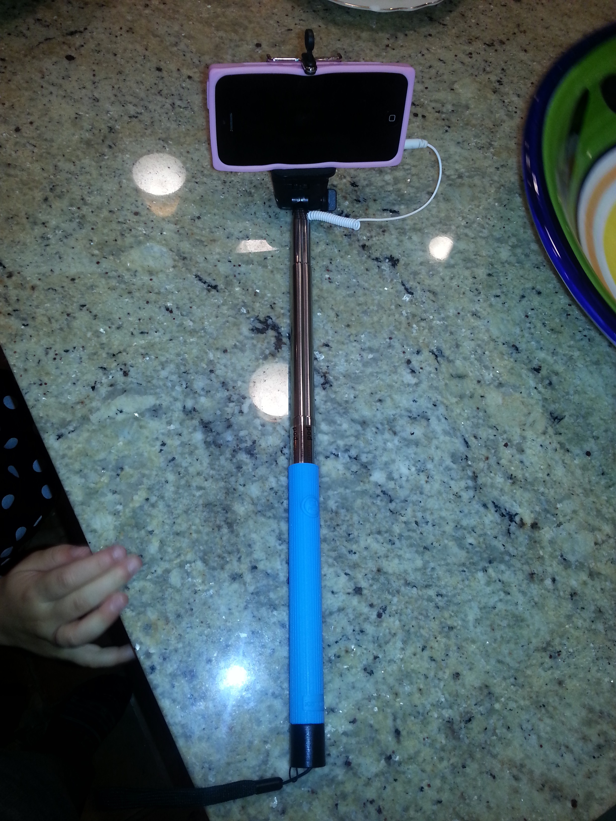 A selfie stick with an iPhone loaded into the clamp.  This selfie stick uses a headphone jack to connect the phone with the buttons on the handle.